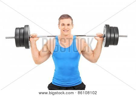 Young smiling athlete in blue shirt exercising with a heavy weight isolated on white background