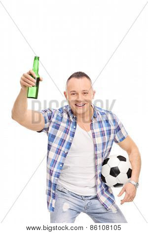 Vertical studio shot of a young man holding a football and a beer bottle and cheering isolated on white background