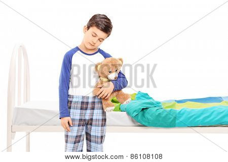 Sleepy boy holding a teddy bear and standing in front of a his bed isolated on white background