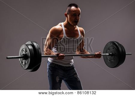 Strong muscular man lifting a heavy barbell on dark grey background