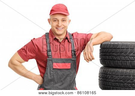 Young male mechanic leaning on a bunch of tires and posing isolated on white background
