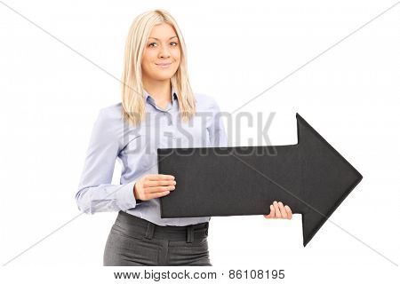 Blond smiling woman holding a big black arrow pointing right isolated on white background