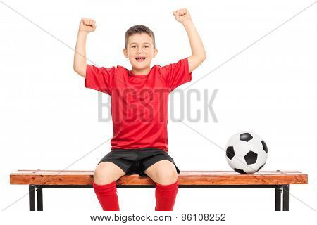 Joyful junior soccer player in red shirt gesturing happiness seated on wooden bench isolated on white background
