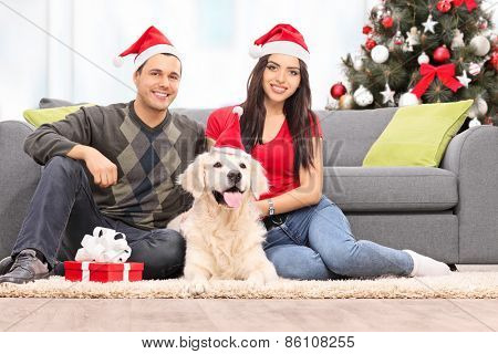 Young couple celebrating Christmas with their dog at home