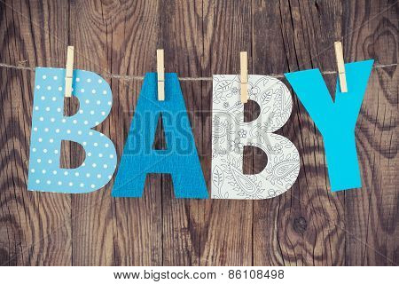 Letters Of Word Baby Hanging On Clothesline Against Wooden Background
