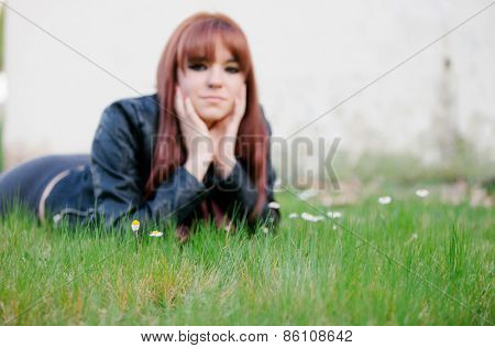 Rebellious teenager girl with red hair lying on the grass. Focus in grass