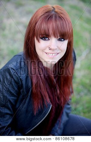 Rebellious teenager girl with red hair sitting on the grass