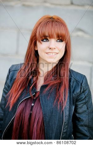 Rebellious teenager girl with red hair smiling and leaning on a wall