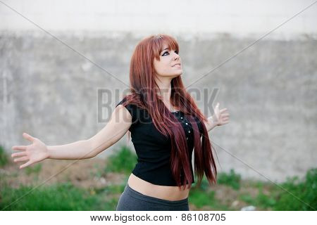 Rebellious teenager girl with open arms facing the sky