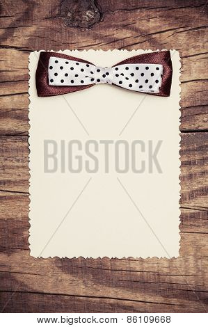 Blank Paper Sheet With Brown And White Polka Dot Bow On Wooden Background