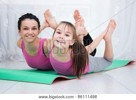 Mother And Daughter Doing Exercise