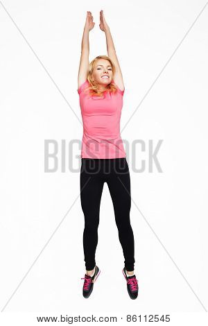 Excited sporty woman jumping. Studio shot.