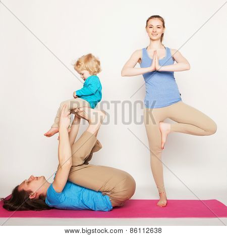 mother, father and son doing yoga over white background