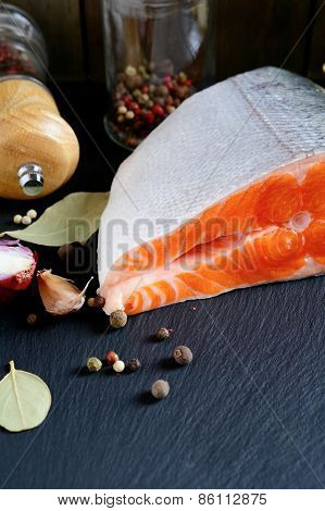 Raw Fresh Salmon Steak With Spices And Lemon On Slate