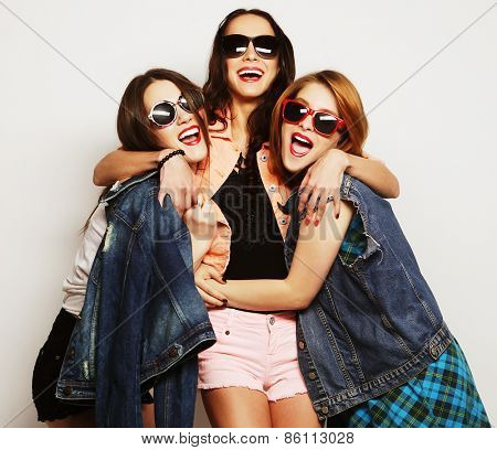 Fashion portrait of three stylish sexy hipster girls best friends, over gray background. Happy time for fun.