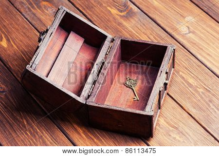 Vintage Key Inside Old Treasure Chest On Wooden Background
