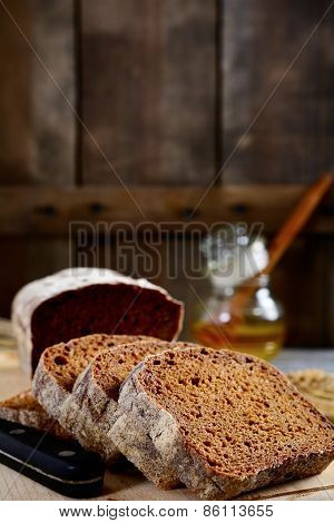 Slices Of Rye Bread And Honey On A Wooden Background