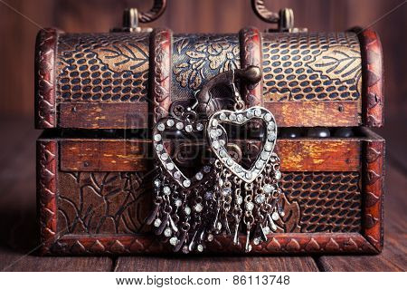 Vintage Earrings In A Form Of Hearts Hanging On Old Treasure Chest
