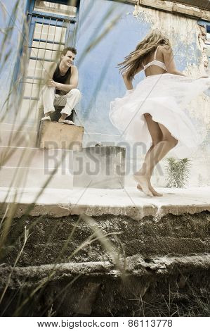 Young happy couple dancing and flirting outdoors on house verandah