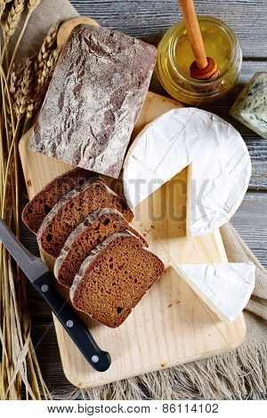 Black Bread With Brie Cheese On A Cutting Board