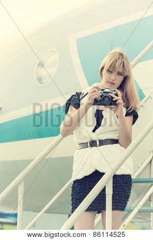 Beautiful Woman With Vintage Camera Posing On Plane Gangway
