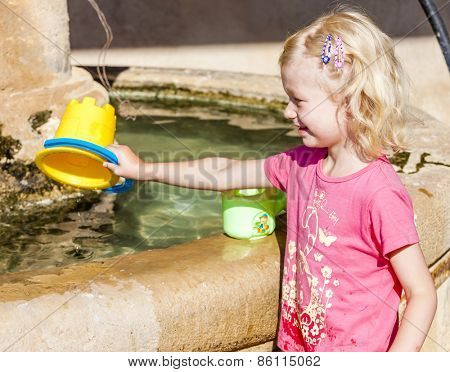 little girl playing at fountain, Ajonc, Provence, France