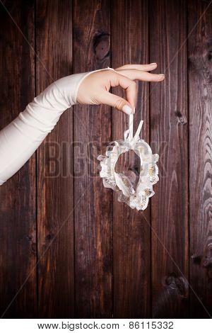 Bride Holding A Garter Against Wooden Background