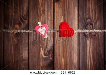 Two Red Hearts Hanging On Clothesline Against Wooden Background