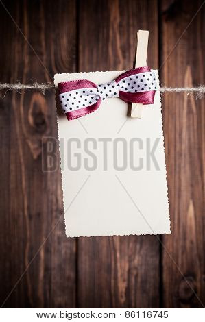 Old Paper Sheet With Bow Hanging On Clothesline Against Wooden Background