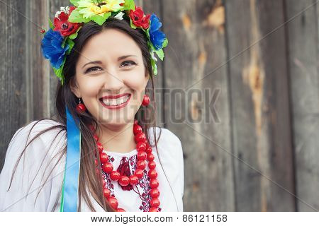 Beautiful Young Woman Wearing National Ukrainian Clothes Sitting In Wooden Hut