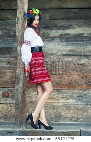 Beautiful Young Woman Wearing National Ukrainian Clothes Posing Near Wooden Hut