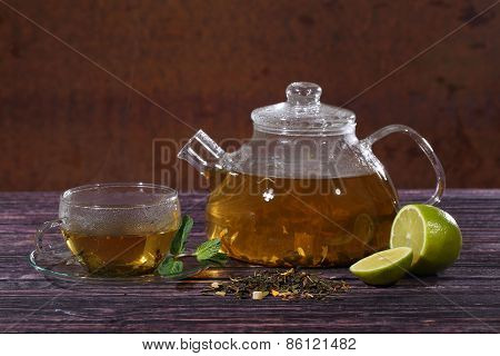 The Chinese Grassy Tea In A Transparent Teapot With Mint And Lime