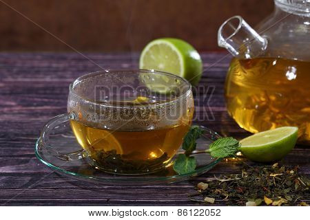 Glass Teapot And Transparent Cup With Tea With Addition Of Mint And Lime