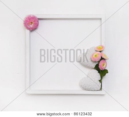 White wooden frame for a background or greeting card with two hearts and daisy flowers.