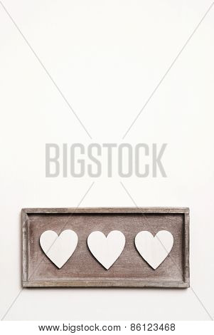 White wooden vintage background with three hearts.