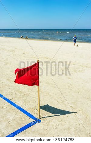 Red Flag On The Beach And A Boy With A Ball