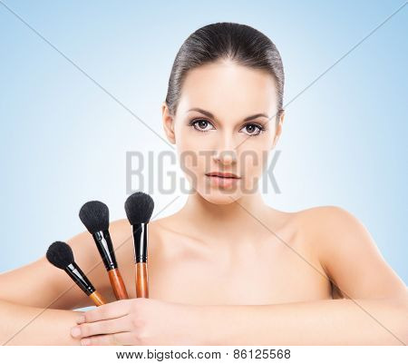 Beauty portrait of young, attractive, fresh, healthy and natural woman with the makeup brushes