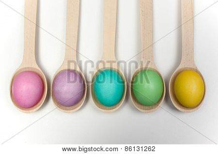 Row Of Easter Eggs On Wooden Spoons Isolated White