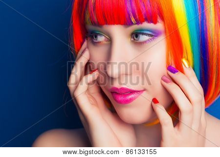 Beautiful Woman Wearing Colorful Wig And Showing Colorful Nails Against Blue Background