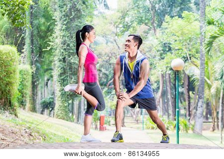 Asian woman and man, a couple, during gymnastics stretching for sport fitness in tropical park