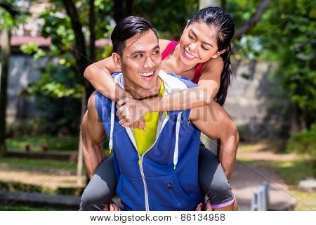 Asian man carrying his girlfriend piggyback for sport in a break during his sport training