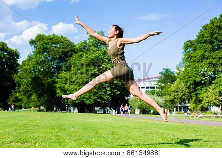 Woman doing jump in park