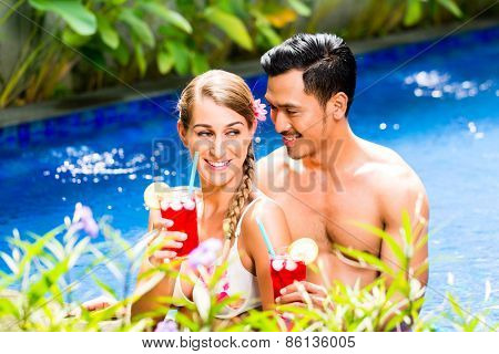 Couple in vacation, Asian man and Caucasian woman, in tropical garden bathing in hotel pool with drinks or cocktails