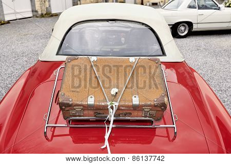 Suitcase Placed On The Trunk Of A Red Car