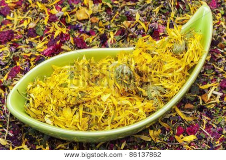 Dry calendula in bowl with dry herbal tea around