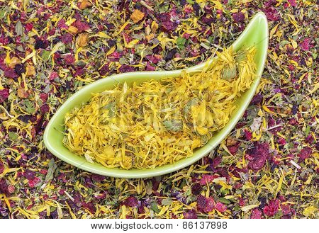 Dry calendula in green bowl with herbal tea around