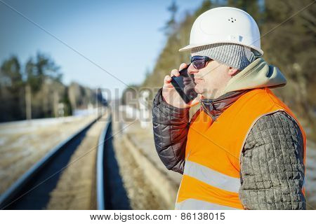 Railway engineer talking on the cell phone on railway