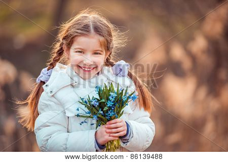 happy little girl smiling and holding a bouquet of blue  flowers