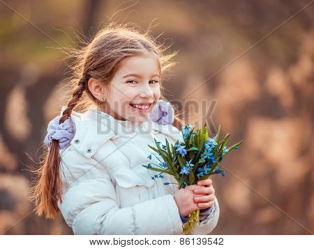 cute little girl smiling and holding a bouquet of blue  snowdrops