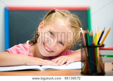 cute little girl at the desk with a blue pen